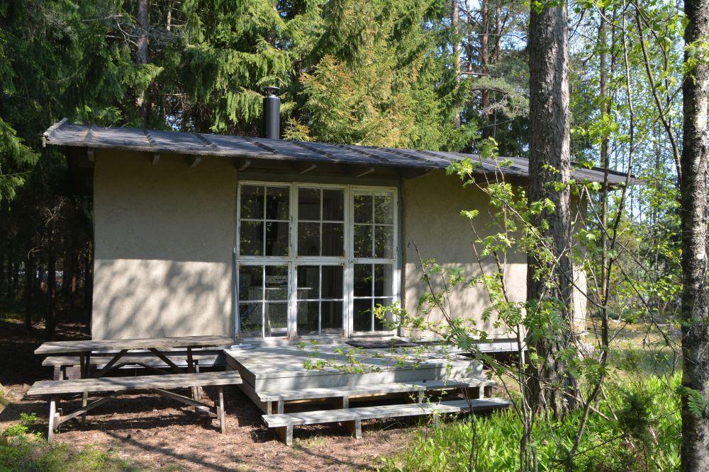 En liten vit stuga med ett stort fönster står i en skog.