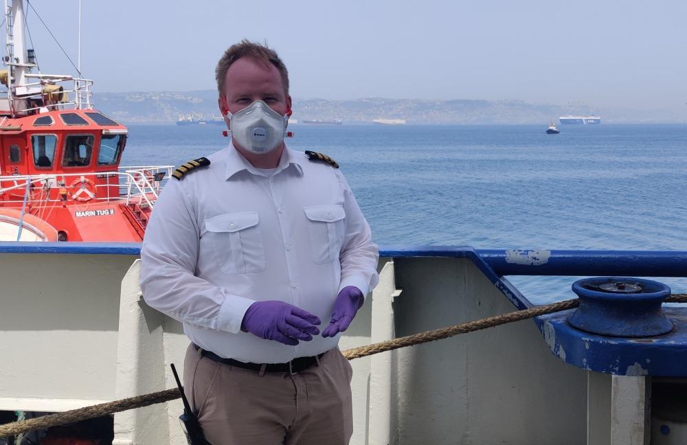 Sjökapten med handskar och munskydd ombord skepp. Turkiets kust i bakgrunden