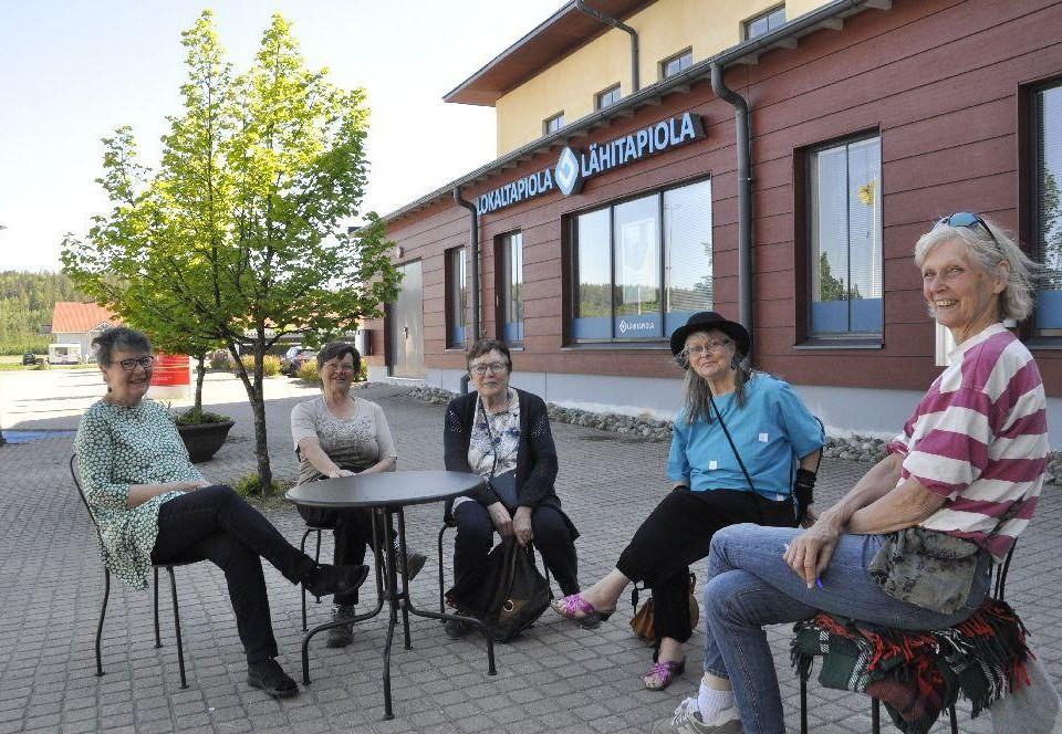 Fem damer sittande på stolar med gott om mellanrum på en innergård