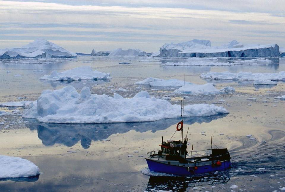 En båt intill flera isflak.