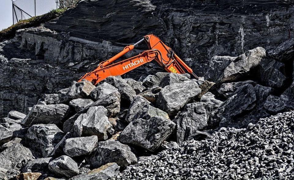 Grävmaqskin bland stora stenblock.