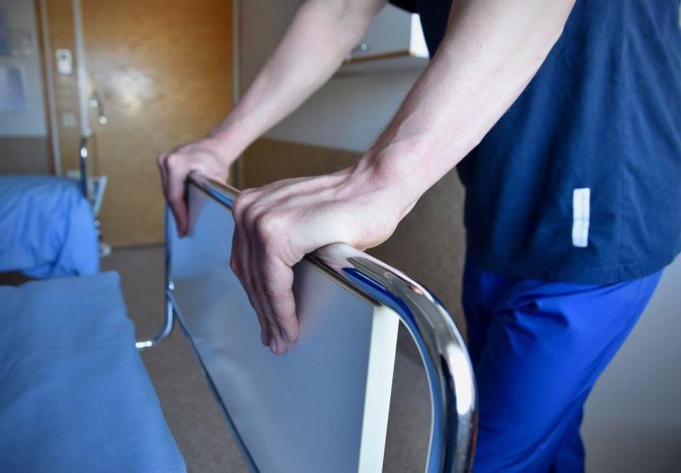 En vårdare skjuter på en sjukhussäng.