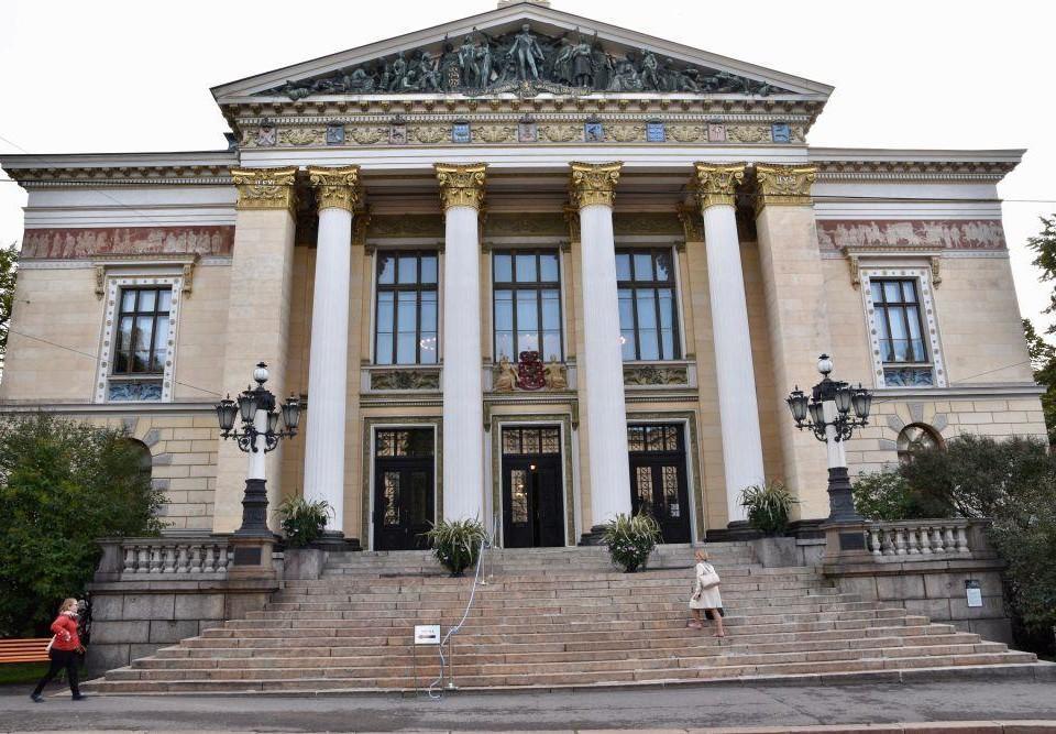 Ett stort neoklassiskt hus med breda trappor och pelare.