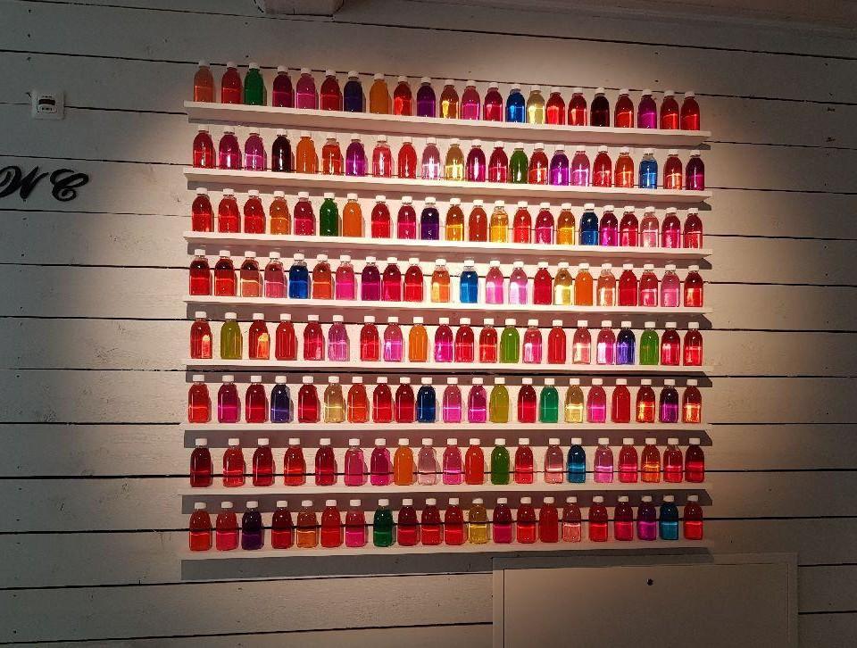 vägg fylld med små glasflaskor på små hyllor fyllda med olika färgers vätskor.