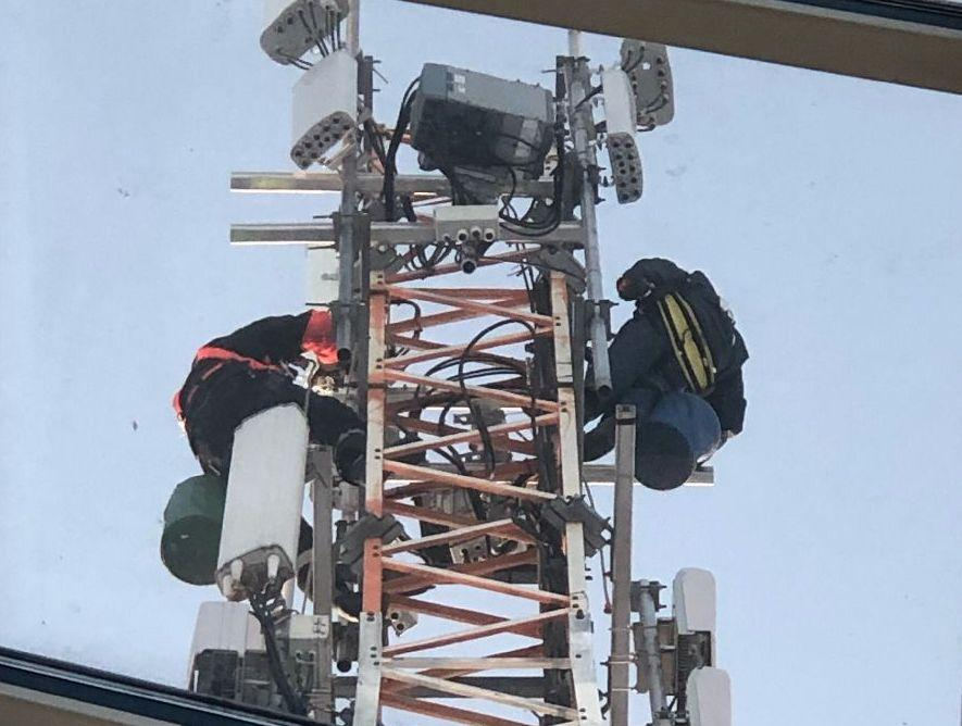 En mast, där 2 personer jobbar klättrande