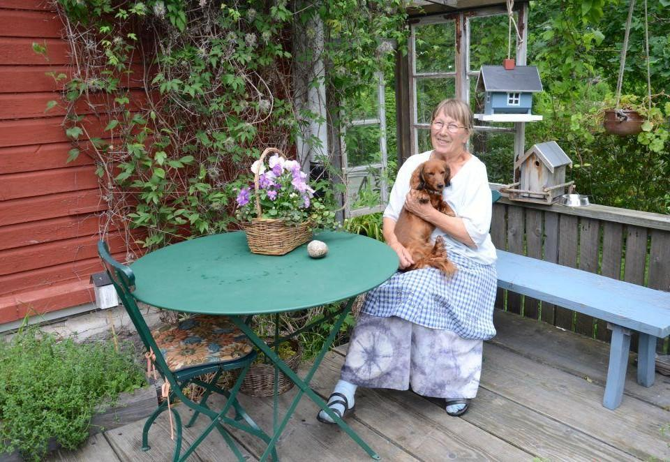 En kvinna sitter utomhus med hund.