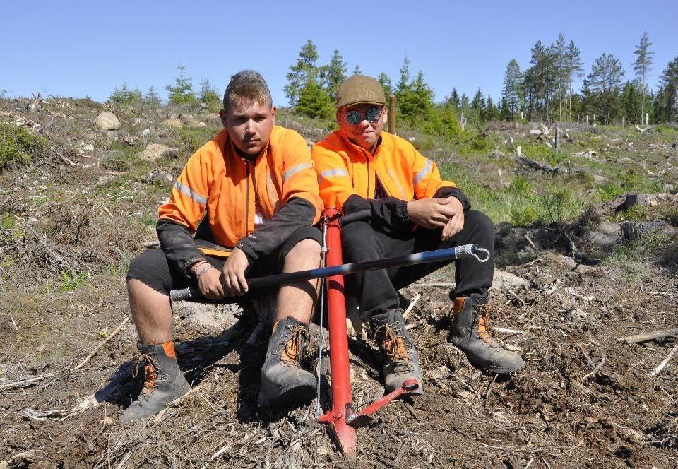 Två unga män sitter på en stubbe med planteringsverktyg med sig