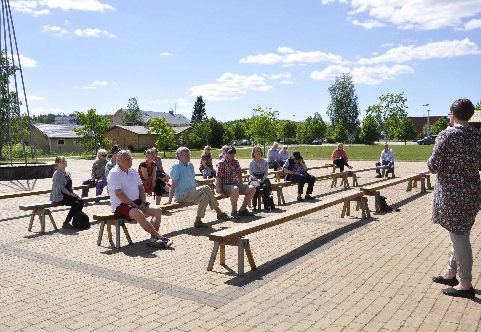 Ett torg fyllt med bänkar. Cirka 15 personer sitter på dem