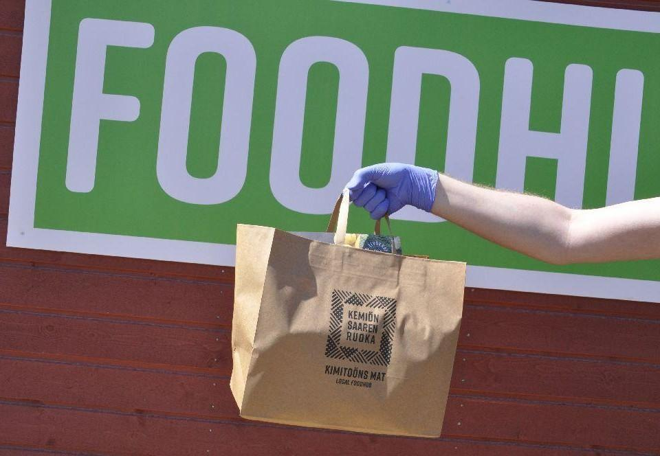 arm med en fylld kasse. Bakom syns en del av en grön skylt med texten foodhub.