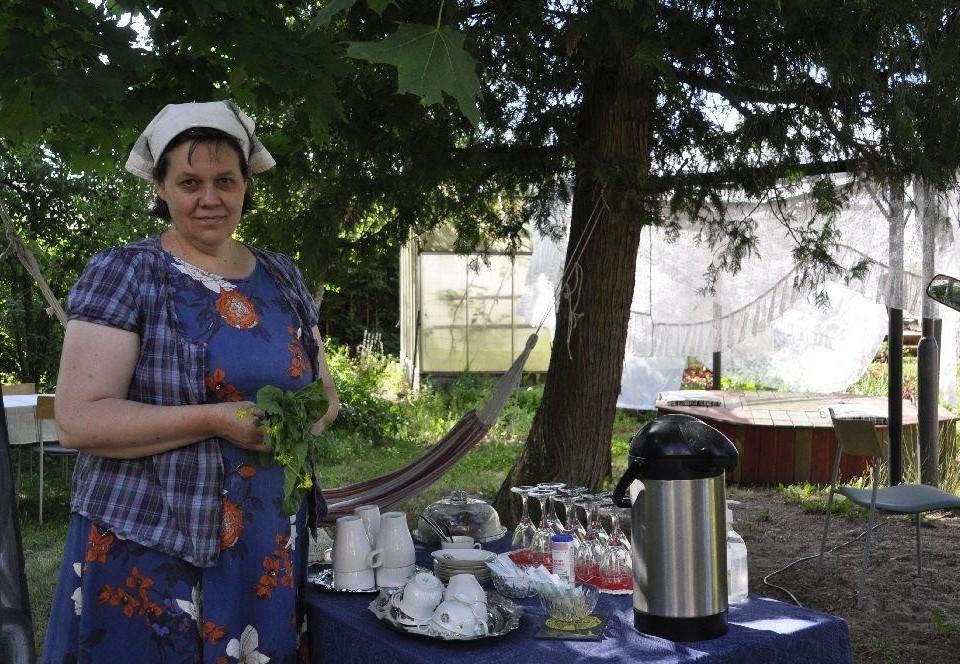 Cafévärdinna vid ett bord med kärl i en trädgård