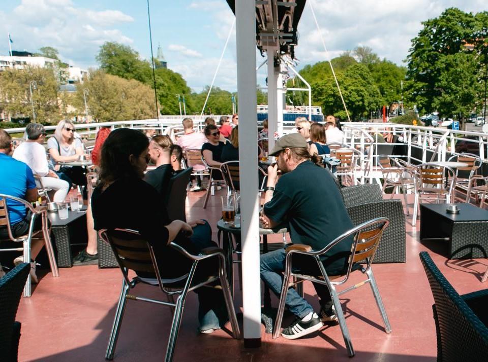 övre däck på restaurangbåt. Hälften av platserna fyllda.
