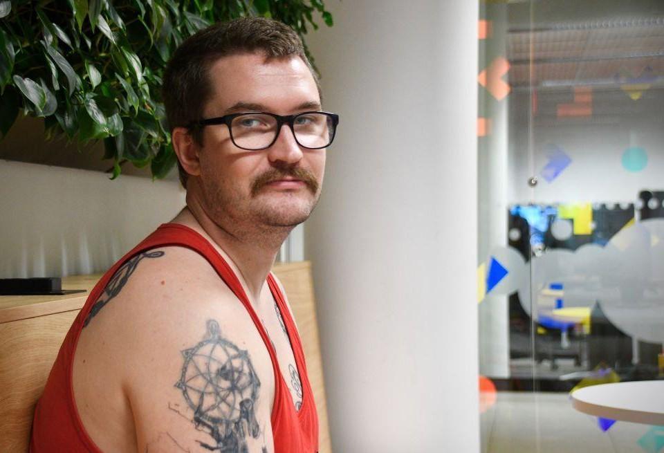 Porträtt av en tatuerad man som ser seriös ut.