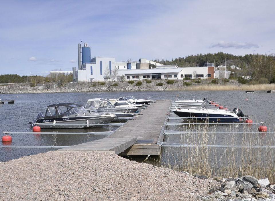I bakgrunden syns fabriksbyggnad. Framför en vik och en brygga med båtar.