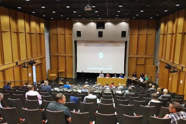 Auditorium med ledamöter långt från varandra. LÄngst ner syns ordförande, sekreterare etc, plus ett videoinspelningsteam.