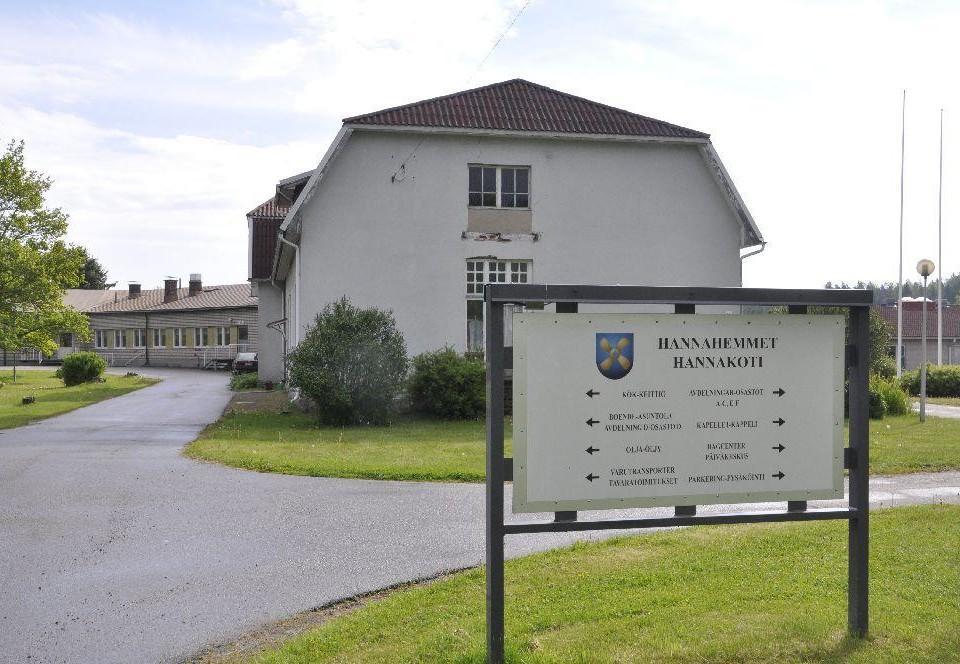En infoskylt om var olika delar av Hannahemmet finns. Bakom syns ett gammalt hus.