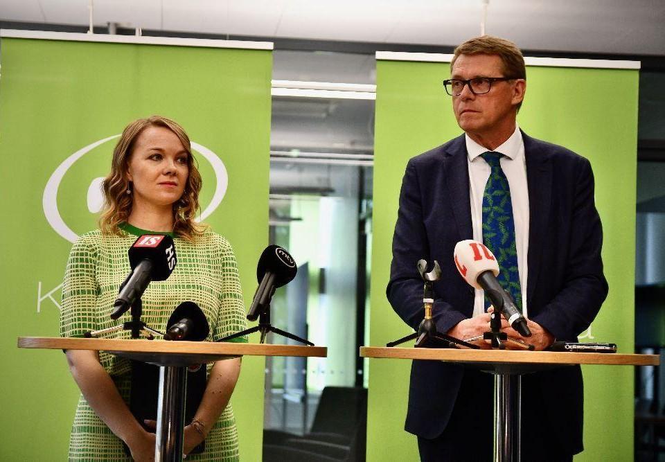 Två personer står vid små bord med mikrofoner