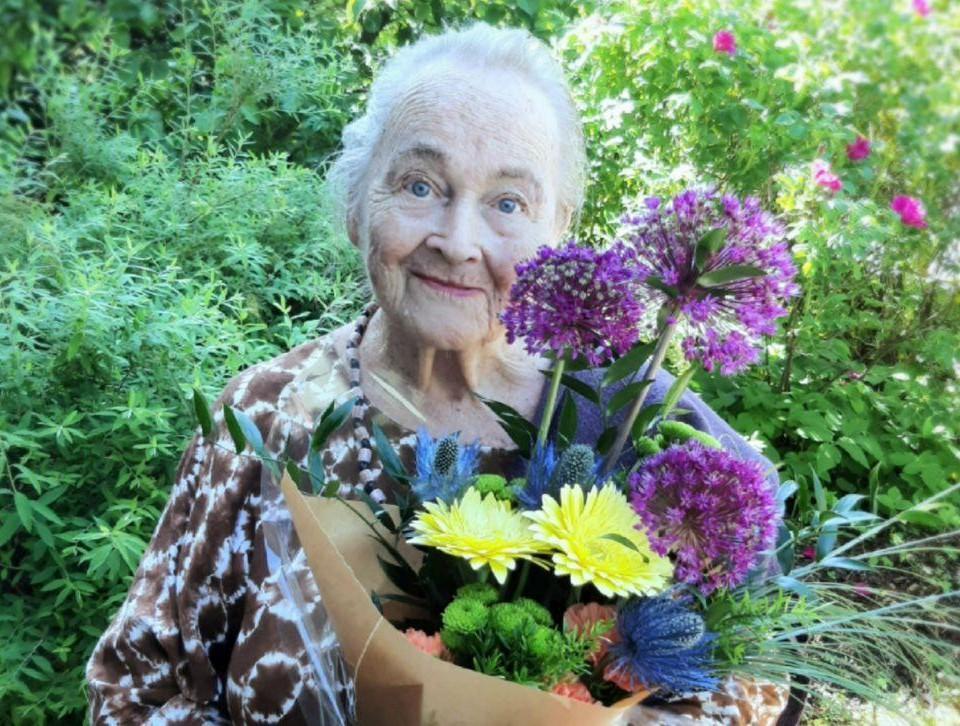 Porträtt av en äldre kvinna med en bukett blommor i famnen