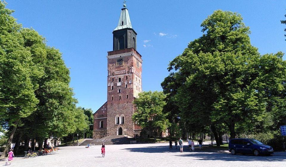 Ett kyrkotorn omringat av gröna träd. Framför kyrkan går och cyklar människor.