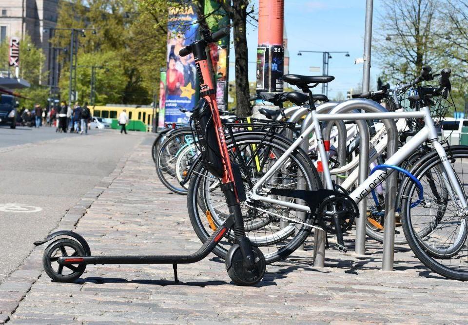 En elsparkcykel står parkerad intill flera cyklar i stadsmiljö.