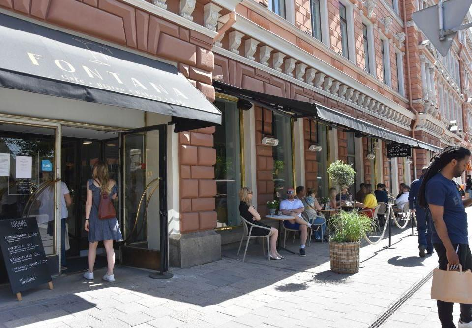 Uteservering och ingång till en restaurang. På markisen över ingången står restaurangens namn, Fontana, och på uteserveringen sitter fullt med folk.
