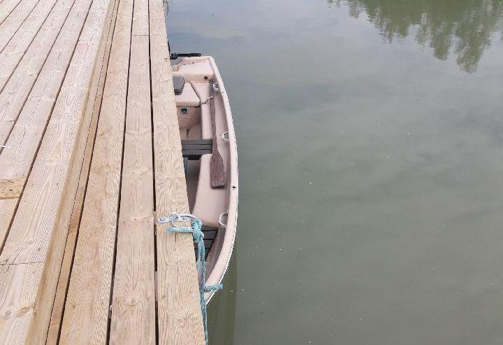 En roddbåt som ligger halvt under en brygga.