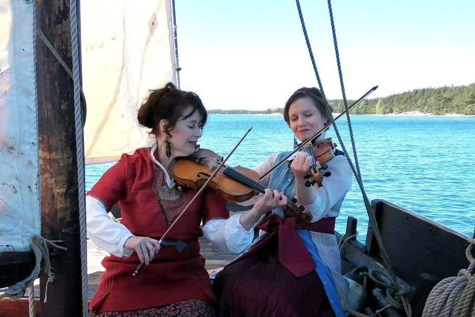 Två kvinnor i traditionella kläder sitter ombord en segelbåt och spelar fiol.