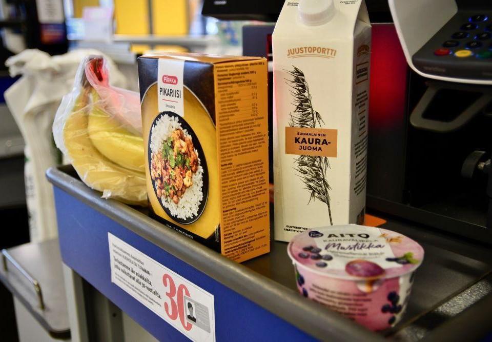 Matvaror som bananer, ris, havremjölk och kvarg på ett rullband i en matbutik.