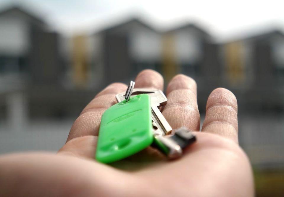 En utsträckt hand som håller i en knippe med nycklar.