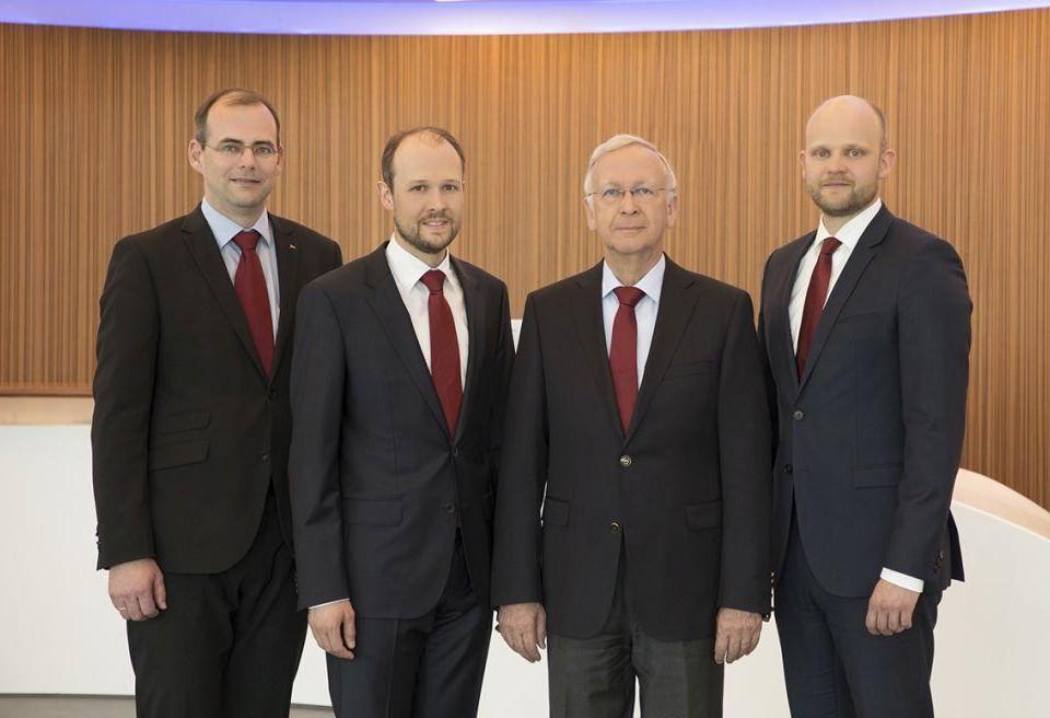 Fyra män klädda i svarta kostymer står intill varandra.