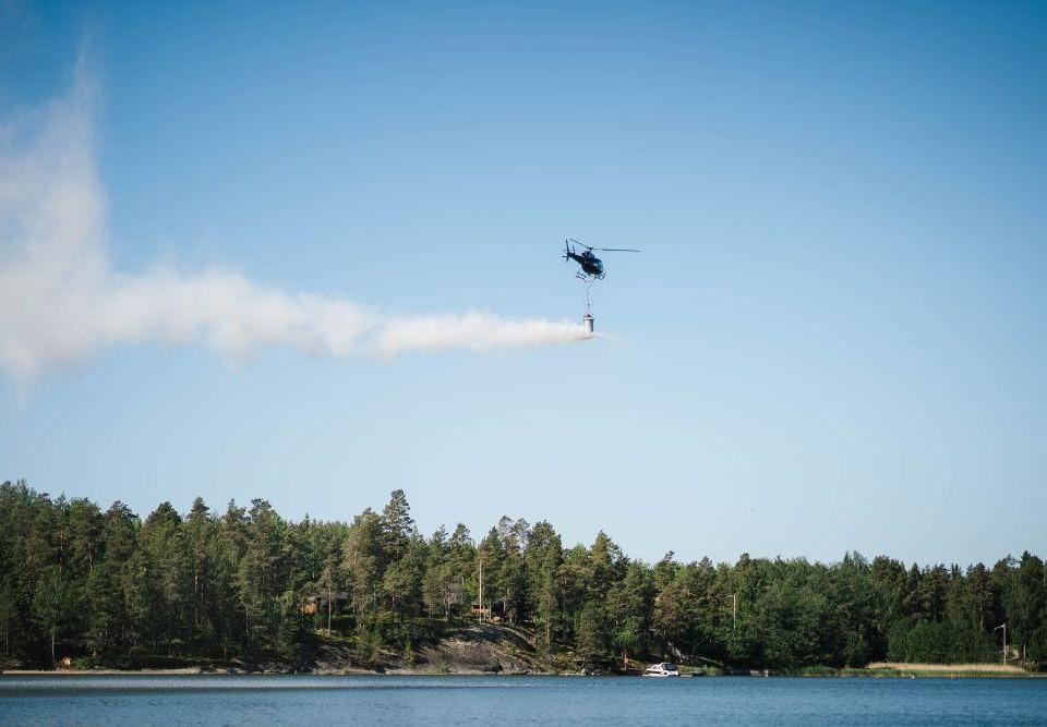 Helikopter släpper ut kalksten ovanför vatten.
