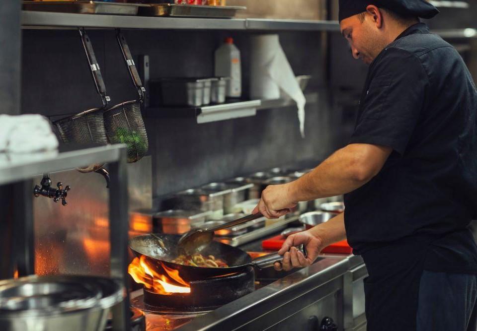 En restaurangkock står och steker.