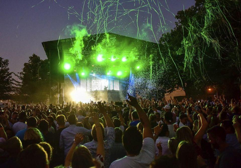 En publik står framför en festivalscen upplyst i grönt med konfetti sprutandes över människomassorna.