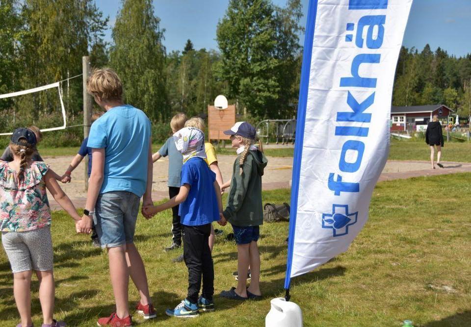 """Barn som håller hand ute på en gräsmatta. På gräsmattan står även en vit flagga med texten """"folkhälsan"""" skriven i blått."""