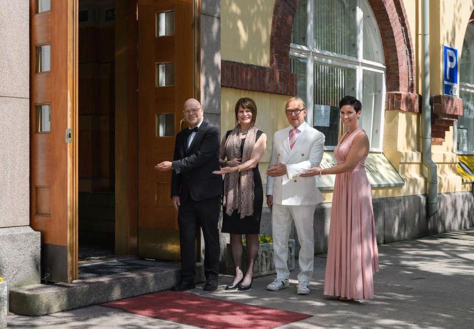 Fyra finklädda personer står intill en öppen dörr och bjuder med en handgest tittaren att kliva in genom dörren.