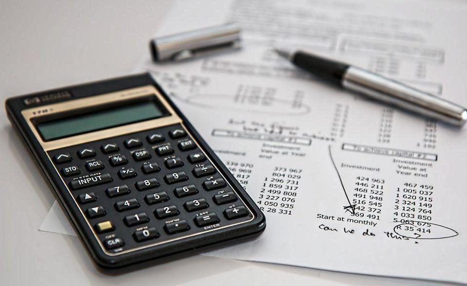 En miniräknare och ett papper med uträkningar ligger på ett bord.