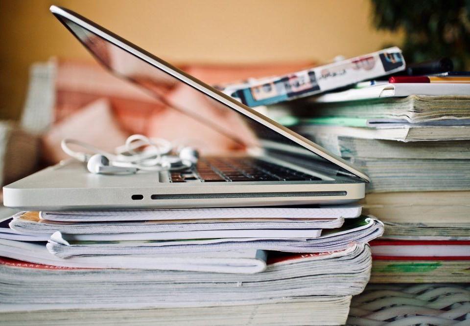 Ovanpå en hög med böcker och papper står en laptop och ett par hörlurar.