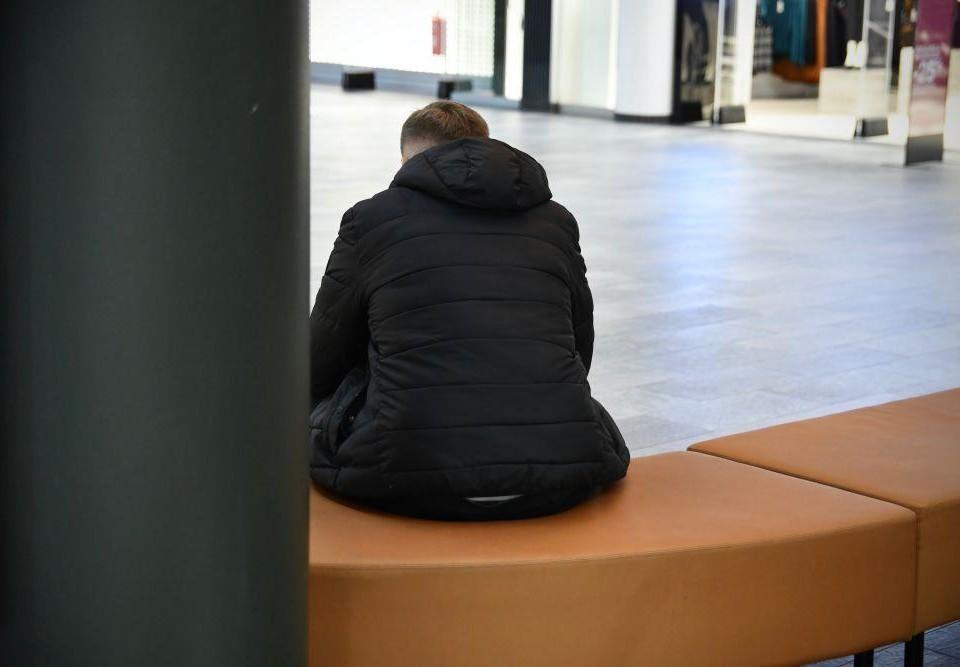 Ryggen av en person som sitter ensam hukad på en bänk.