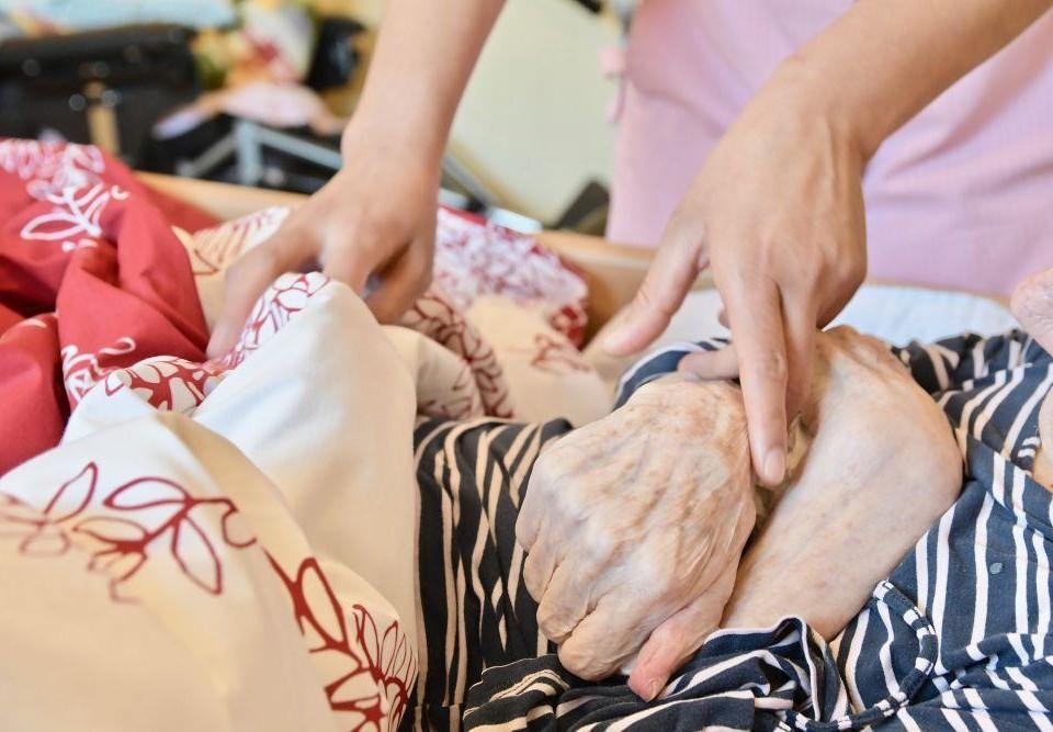 Vårdares och äldres händer på en säng