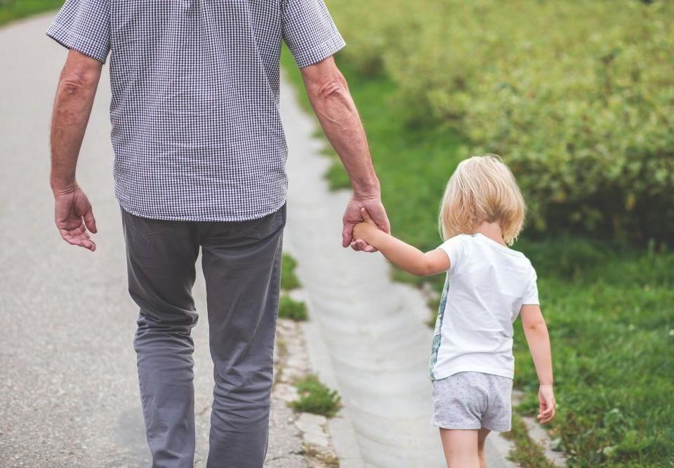 ett barn håller en vuxen person i handen. De går längs med landsväg med ryggen åt kameran.