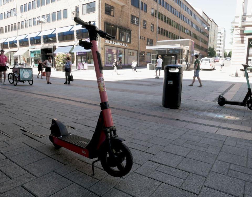 en voi-elsparkcykel parkerad vid gata.