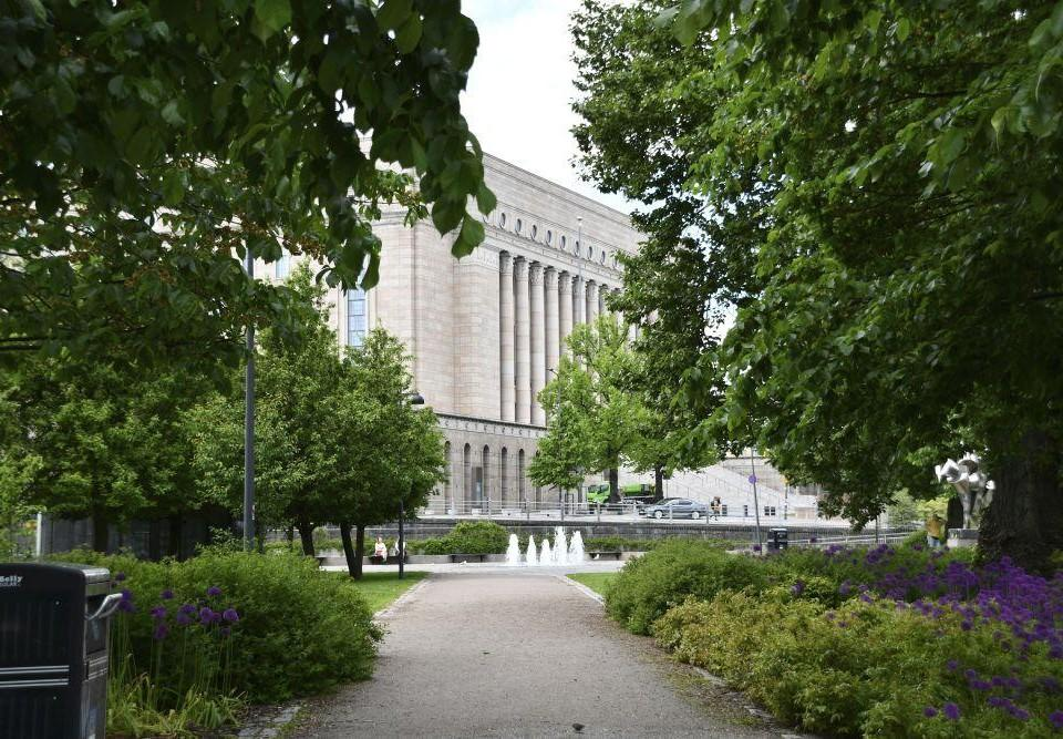 Riksdagshuset omgivet av gröna buskar och träd.