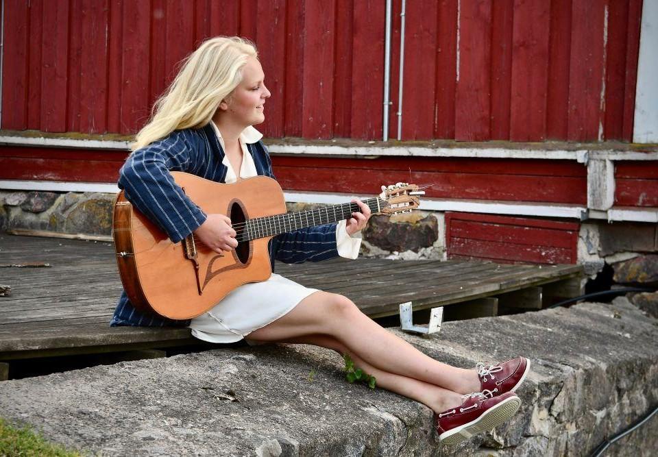 Ung ljushårig kvinna sitter på en klippa med en gitarr i famnen.