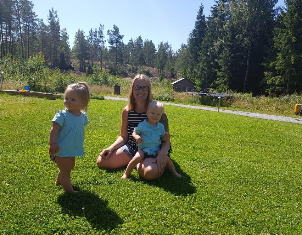 kvinna med barn på gräsmatta