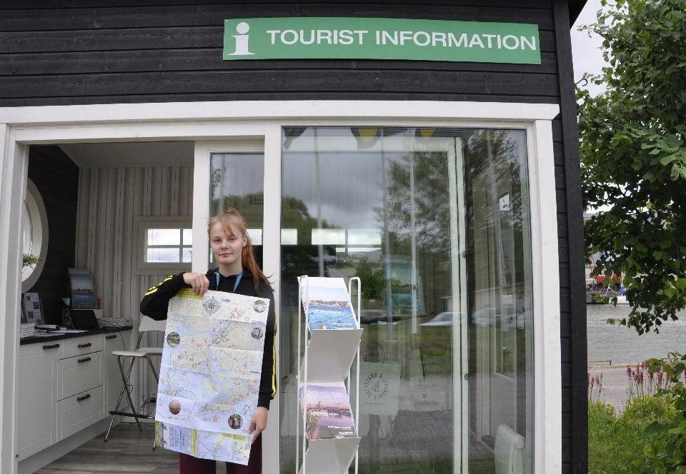 Ung dam utanför infokiosk med en stor karta i handen.
