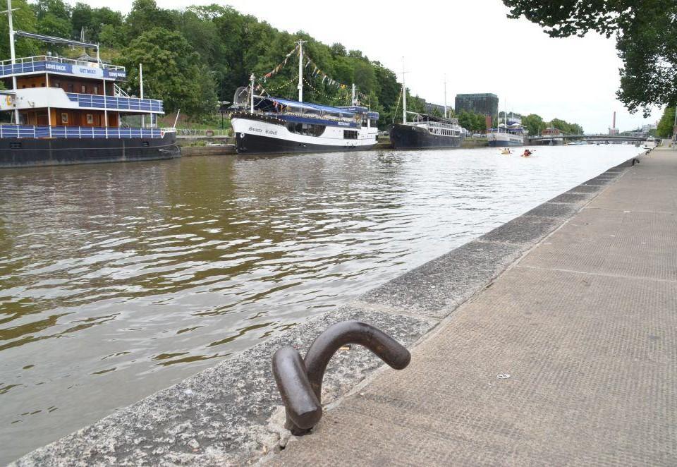 Aura å med kajkanten i förgrunden och restaurangbåtar i bakgrunden.