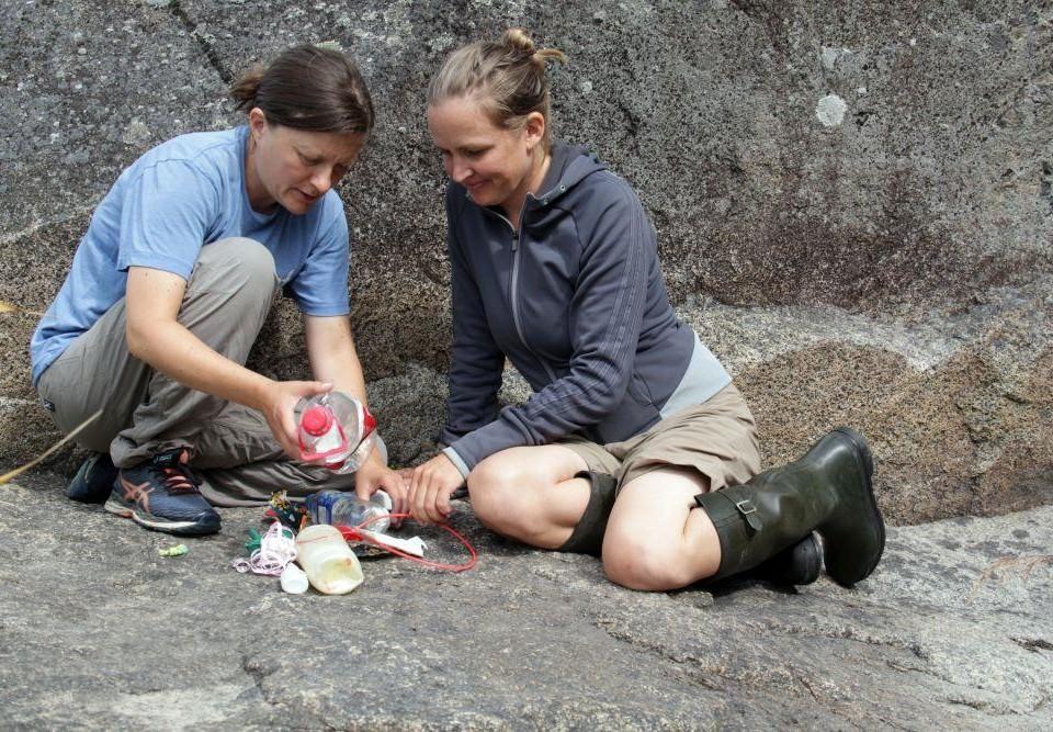 Två kvinnor sitter på ett berg och sorterar skräp.
