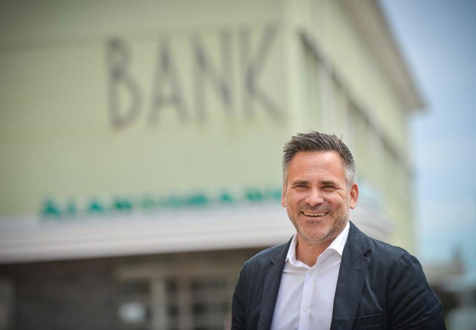 """Porträtt av kostymklädd man framför ett hus med texten """"Bank"""" på."""