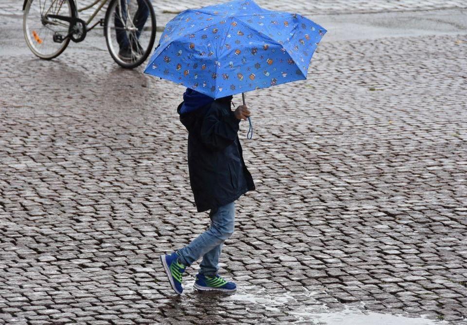 människa med paraply på ett torg