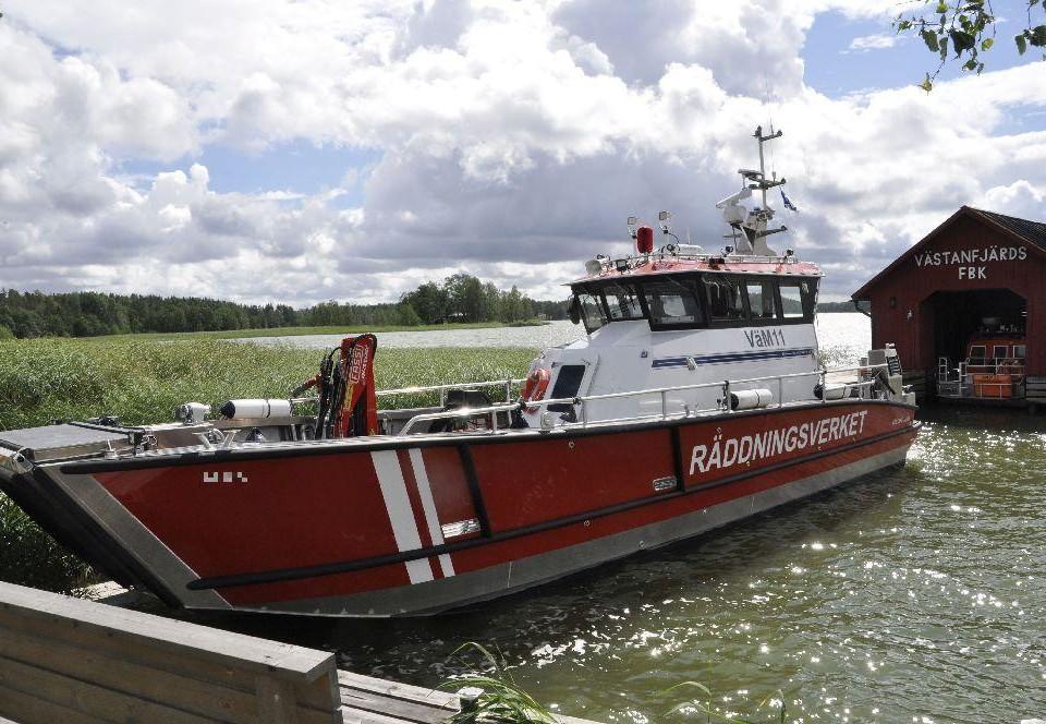 Räddningsbåt vid en brygga. Bakom syns ett båthus med texten Västanfjärd FBK.