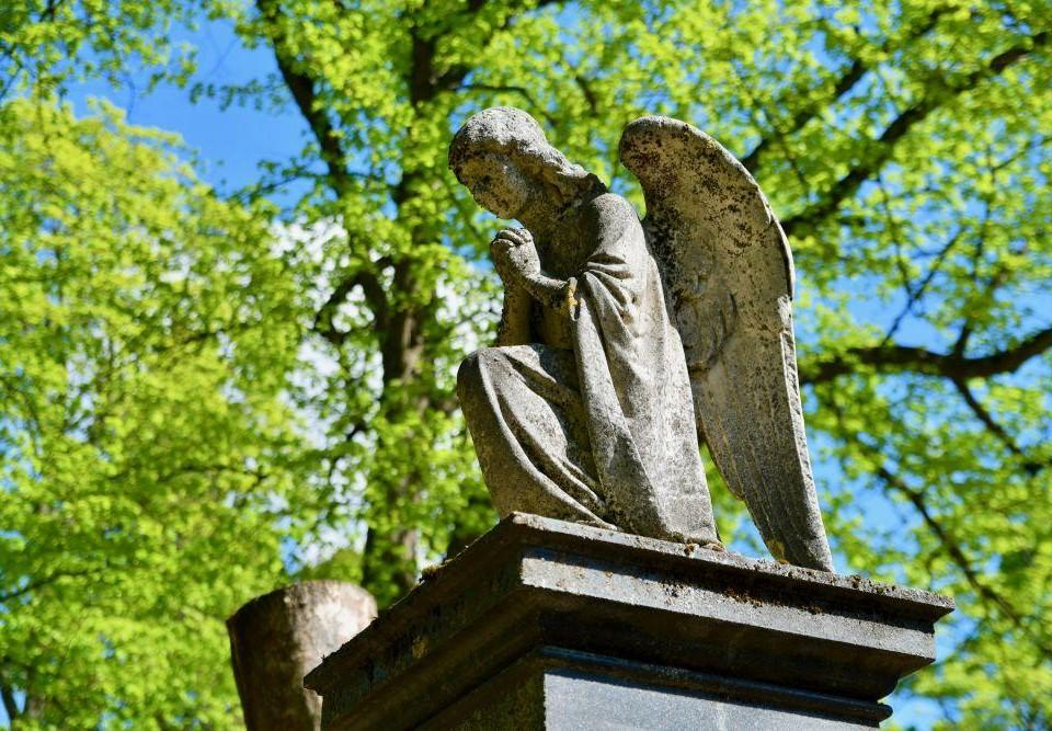 Ängel av marmor på en piedestal på en gravgård.